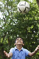 Young boy looking up and trying to catch the ball - Asia Images Group