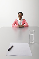young woman sitting on end of the table waiting to be interviewed - Asia Images Group