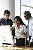 Indian woman looking at a computer with male colleagues - Asia Images Group