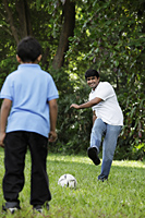 Father kicking ball to son - Asia Images Group