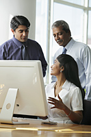 Indian business people talking to each other around a computer - Asia Images Group
