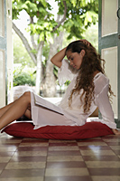 Young woman with long hair sitting on floor - Asia Images Group
