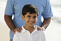 Cropped shot of father's hands on smiling son's shoulders - Asia Images Group