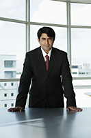 Indian businessman standing behind desk - Asia Images Group