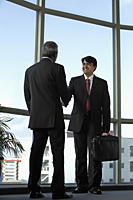 Indian business men shaking hands and smiling - Asia Images Group