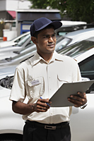Security guard writing on clipboard - Asia Images Group