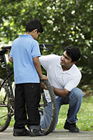 Father and son fixing bike together - Asia Images Group