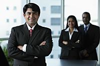 Indian business man standing in front of colleagues - Asia Images Group