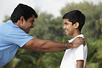 Father and son looking at each other and smiling outdoors. - Asia Images Group
