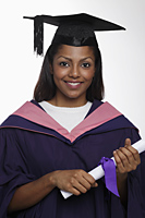 Young woman wearing graduation cap and gown and holding diploma - Asia Images Group