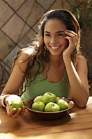 Young woman with a bowl of green apples smiling - Asia Images Group