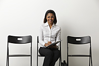 Young Indian woman fills out form and waits in waiting room - Asia Images Group
