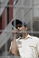 Security guard talking on walkie talkie - Asia Images Group