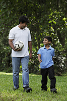 Father and son walking together in park holding ball - Asia Images Group