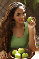 Young woman with bowl of green apples smiling - Asia Images Group