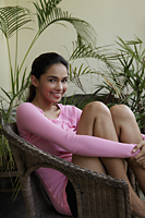 Young woman holding her knees and smiling - Asia Images Group