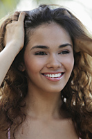 young woman smiling with hands in her hair - Asia Images Group