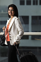 woman holding bag and suitcase, smiling - Asia Images Group
