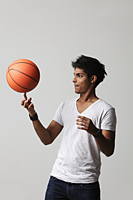 young man twirling basket ball on his finger - Asia Images Group