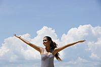 young woman lifting up her arms with blue sky and clouds background - Asia Images Group