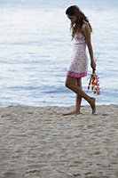 young woman walking on beach holding pink flowers - Asia Images Group
