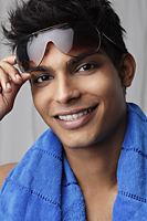 head shot of young man holding sunglasses and wearing a towel around his neck - Asia Images Group