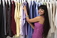 woman looking at rack of clothes and smiling - Asia Images Group