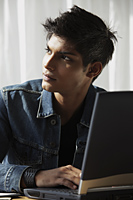 young man at laptop looking away - Asia Images Group
