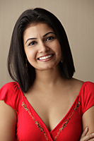 head shot of woman smiling wearing a red dress - Asia Images Group