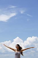 happy young woman raising her arms, blue sky and clouds background. - Asia Images Group