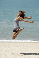 happy young woman jumping in air at the beach - Asia Images Group