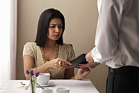 woman sitting at a cafe looking concerned over the bill - Asia Images Group