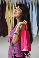woman holding pink shopping bag and smiling - Asia Images Group