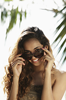 young woman looking out from sunglasses - Asia Images Group