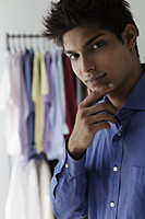 young man looking at camera with shirts in background - Asia Images Group