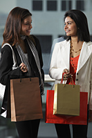 two woman holding shopping bags and looking at each other smiling. - Asia Images Group