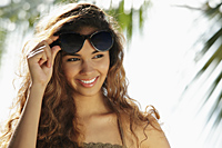 young woman smiling and holding up her sunglasses - Asia Images Group