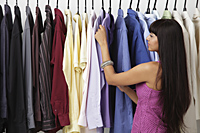 woman looking at rack of clothes - Asia Images Group