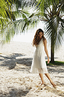 young woman walking in the sand with coconut trees in background - Asia Images Group