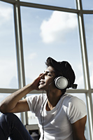 young man with eyes closed looking up wearing headphones - Asia Images Group