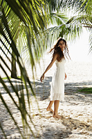 young woman walking on beach with coconut trees in background - Asia Images Group