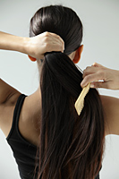 back shot of woman combing her long hair - Asia Images Group