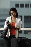 woman holding suitcase and looking at text message - Asia Images Group