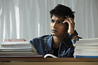 young man reading book and thinking - Asia Images Group