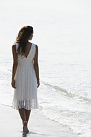 back view of woman wearing a white dress and walking a long the beach - Asia Images Group