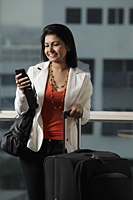 woman holding suitcase looking at phone and smiling - Asia Images Group