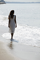 back view of woman wearing white dress and walking along the beach - Asia Images Group