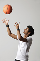 young man throwing basketball into the air - Asia Images Group