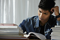 young man reading a book, studying - Asia Images Group
