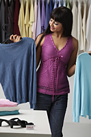 woman looking at a sweater in shop - Asia Images Group